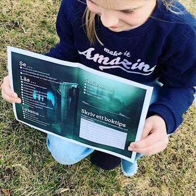 Bild på folder som hålls upp av en tjej